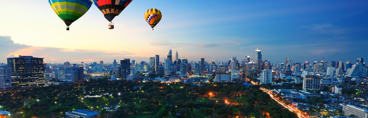 Hot air balloons floating above a city, image used for HSBC foreign exchange global view and global transfers